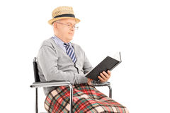 Hogere mens die een boek gezet in rolstoel lezen Royalty-vrije Stock Foto