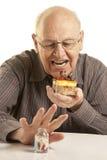 Hogere mens die een cake eet Stock Afbeeldingen