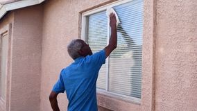 Hogere mens die een huisvenster wassen stock video