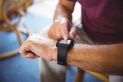 Hogere mens die een slim horloge met behulp van royalty-vrije stock afbeeldingen