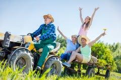 Hogere mens die familie voor rit op tractor nemen Stock Afbeelding