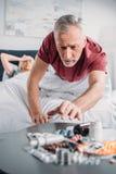 Hogere mens die geneesmiddelen van lijst in slaapkamer nemen stock afbeeldingen