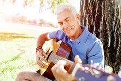 Hogere mens die gitaar in openlucht beoefenen Stock Foto's