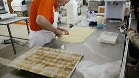 Hogere mens die heerlijk voedsel in bakkerij scherp deeg voorbereiden stock footage