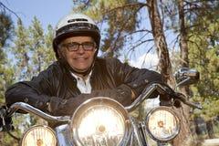 Hogere mens die helm dragen die op motorfietssturen leunen in bos Stock Foto's