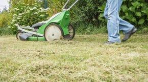 Hogere mens die het gazon met een grasmaaier maaien Royalty-vrije Stock Afbeelding