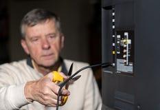 Hogere mens die het koord op zijn kabeltelevisie-pakket snijden stock fotografie