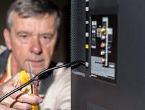 Hogere mens die het koord op zijn kabeltelevisie-pakket snijden Stock Afbeeldingen