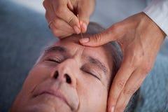 Hogere mens die hoofdmassage van fysiotherapeut ontvangen Royalty-vrije Stock Foto