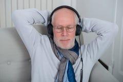 Hogere mens die in hoofdtelefoons aan muziek thuis luisteren stock fotografie