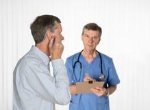 Hogere mens die hoorzittingstest met een arts hebben stock foto