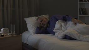 Hogere mens die impatiently komende ochtend wachten, lijdend aan slapeloosheid bij nacht stock footage