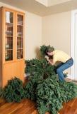 Hogere mens die kunstmatige Kerstmisboom samenbrengen voor KERSTMIS Stock Fotografie