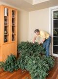 Hogere mens die kunstmatige Kerstmisboom samenbrengen voor KERSTMIS Stock Foto