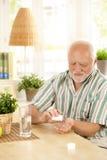 Hogere mens die medicijn thuis neemt Royalty-vrije Stock Fotografie