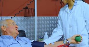Hogere mens die met arts interactie aangaan terwijl het schenken van bloed 4k stock video