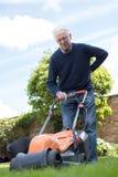 Hogere Mens die met Rugpijn lijden terwijl het Gebruiken van Elektrische Gazonmo royalty-vrije stock fotografie