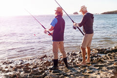 Hogere mens die met zijn kleinzoon vissen stock afbeeldingen