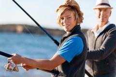Hogere mens die met zijn kleinzoon vissen stock afbeelding