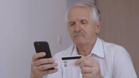 Hogere mens die online met creditcard winkelen die smartphone thuis gebruiken Online bankwezen mobiele app stock videobeelden