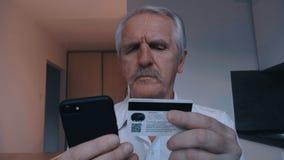 Hogere mens die online met creditcard winkelen die smartphone thuis in keuken gebruiken Online bankwezen mobiele app stock video