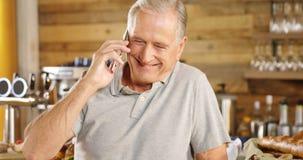 Hogere mens die op de telefoon bij koffie tegen4k spreken stock video