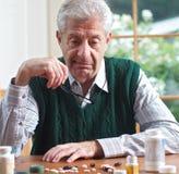 Hogere mens die pillen op een lijst bekijkt Stock Fotografie