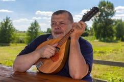 Hogere mens die rust openlucht het spelen mandoline hebben stock foto's