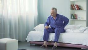Hogere mens die scherpe pijn in rug na ontwaken, slechte slaapvoorwaarden voelen stock video