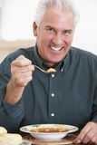 Hogere Mens die Soep eet, die bij de Camera glimlacht Stock Afbeelding