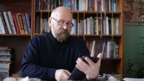 Hogere mens die tablet gebruiken die op een stoel in de bibliotheek zitten stock footage