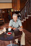 Hogere mens die tabletpc in hotel met behulp van Stock Afbeeldingen