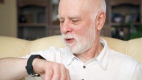 Hogere mens die thuis smartwatch, doorbladeren, die nieuws lezen gebruiken Concept technologiegebruik door oudere mensen stock footage