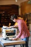 Hogere mens die timmerwerk met het scherpen van vliegtuig op werkbank doen Stock Afbeelding