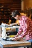 Hogere mens die timmerwerk met het scherpen van vliegtuig op werkbank doen Stock Afbeeldingen