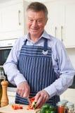 Hogere Mens die van het Koken in Keuken genieten stock foto