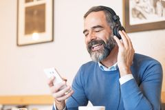Hogere mens die van zijn favoriete muziek genieten Stock Afbeelding