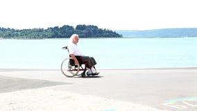 Hogere mens die van zijn rolstoel opstaan stock video