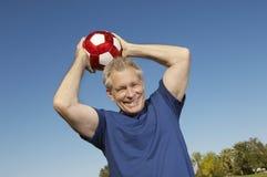 Hogere Mens die Voetbalbal werpen Stock Fotografie