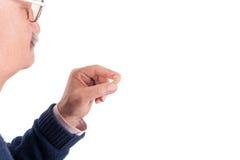 Hogere mens die zijn gehoorapparaat tonen stock afbeelding