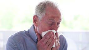 Hogere mens die zijn neus blazen stock footage