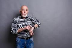 Hogere mens die zijn nieuw slim horloge met behulp van stock afbeelding