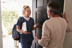Hogere mens die zijn voordeur openen voor een vrouwelijke gezondheidszorgarbeider die een bezoek van de huisgezondheid afleggen royalty-vrije stock afbeeldingen