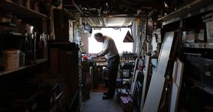 Hogere mens die in zijn workshop werken stock footage