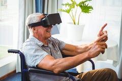 Hogere mens in een rolstoel die een virtueel werkelijkheidsapparaat met behulp van royalty-vrije stock foto's