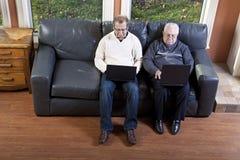 Hogere mens en zijn zoon die laptop computer met behulp van Royalty-vrije Stock Foto