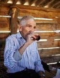 Hogere mens het drinken pruimbrandewijn stock foto