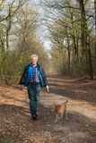 Hogere mens het lopen hond in bos Royalty-vrije Stock Fotografie