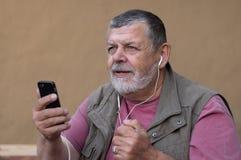 Hogere mens het luisteren muziek van cellulair over hoofdtelefoons terwijl het zitten van openluchtkleimuur stock afbeeldingen