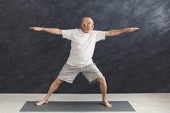 Hogere mens het praktizeren yoga binnen stock foto's